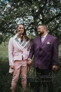 May be an image of 3 people, people standing, suit, tree and outdoors